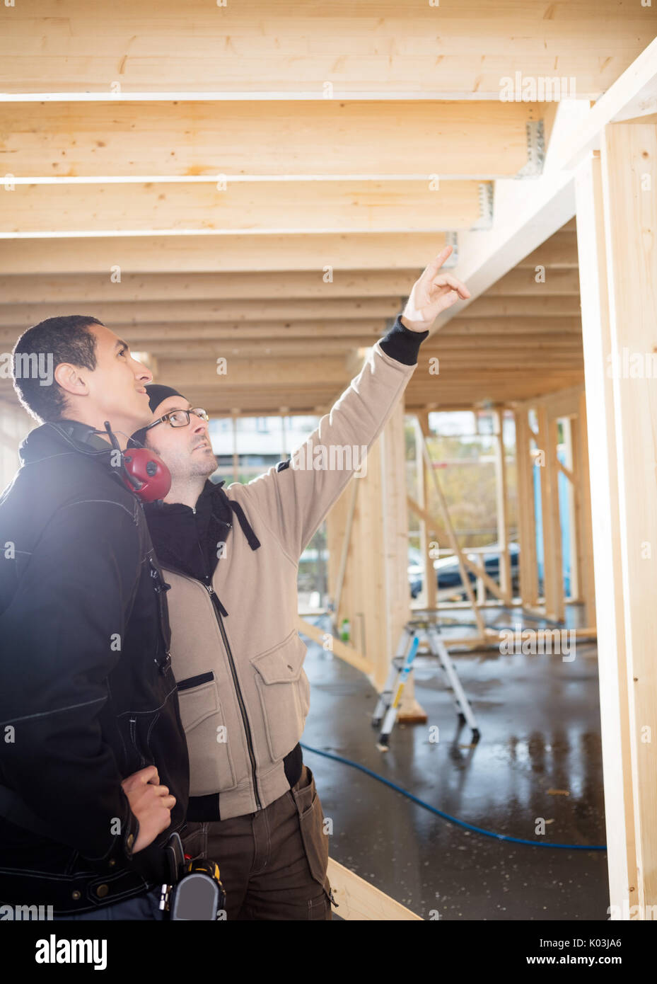 Carpenter Showing Wooden Roof To Colleague At Site - Stock Image