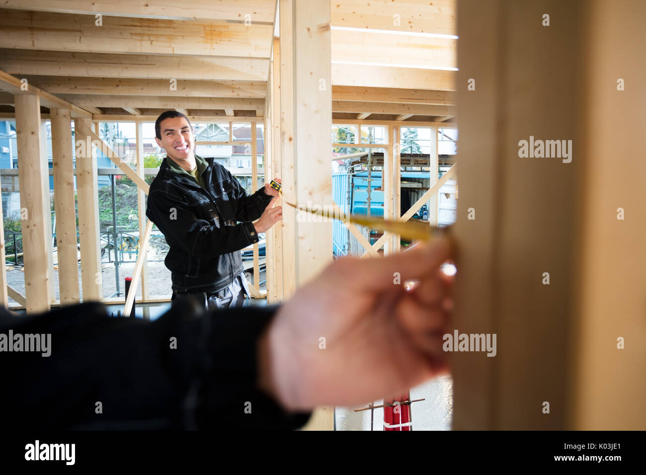 Happy Carpenter Measuring Wood With Help Of Colleague At Site - Stock Image