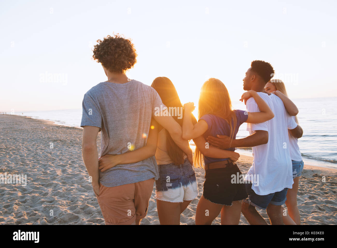 Group of happy friends having fun at ocean beach - Stock Image