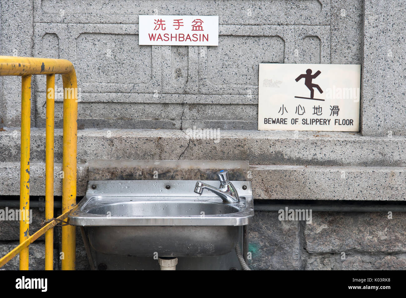 Steel sink hang on stone wall on street in city center. The empty public bathroom in Hong Kong. - Stock Image