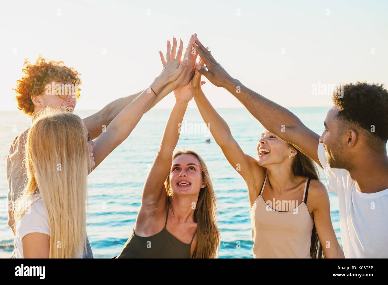 Group of friends having fun on the beach - Stock Image