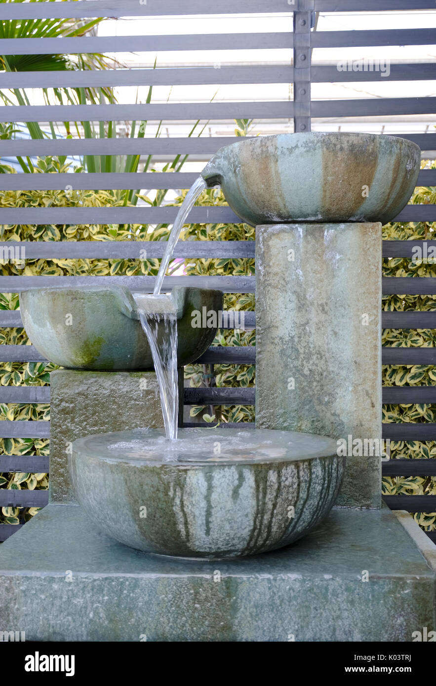 Stone garden fountain with water flowing over 3 bowls. - Stock Image