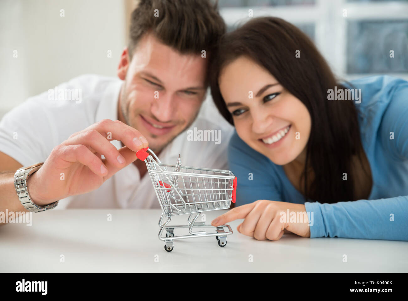 Close-up Of Smiling Young Couple Looking At Miniature Empty Shopping Cart - Stock Image
