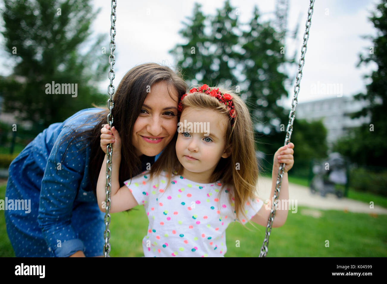 Young mother plays in the playground with the little daughter. Woman shakes the baby on a swing. City court yard. Serene summer day. Good mood. - Stock Image