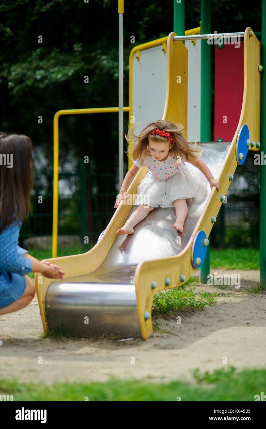Mom and her little daughter are playing on the playground. Charming baby sliding down a slide at the playground. City court yard. Serene summer day. G - Stock Image