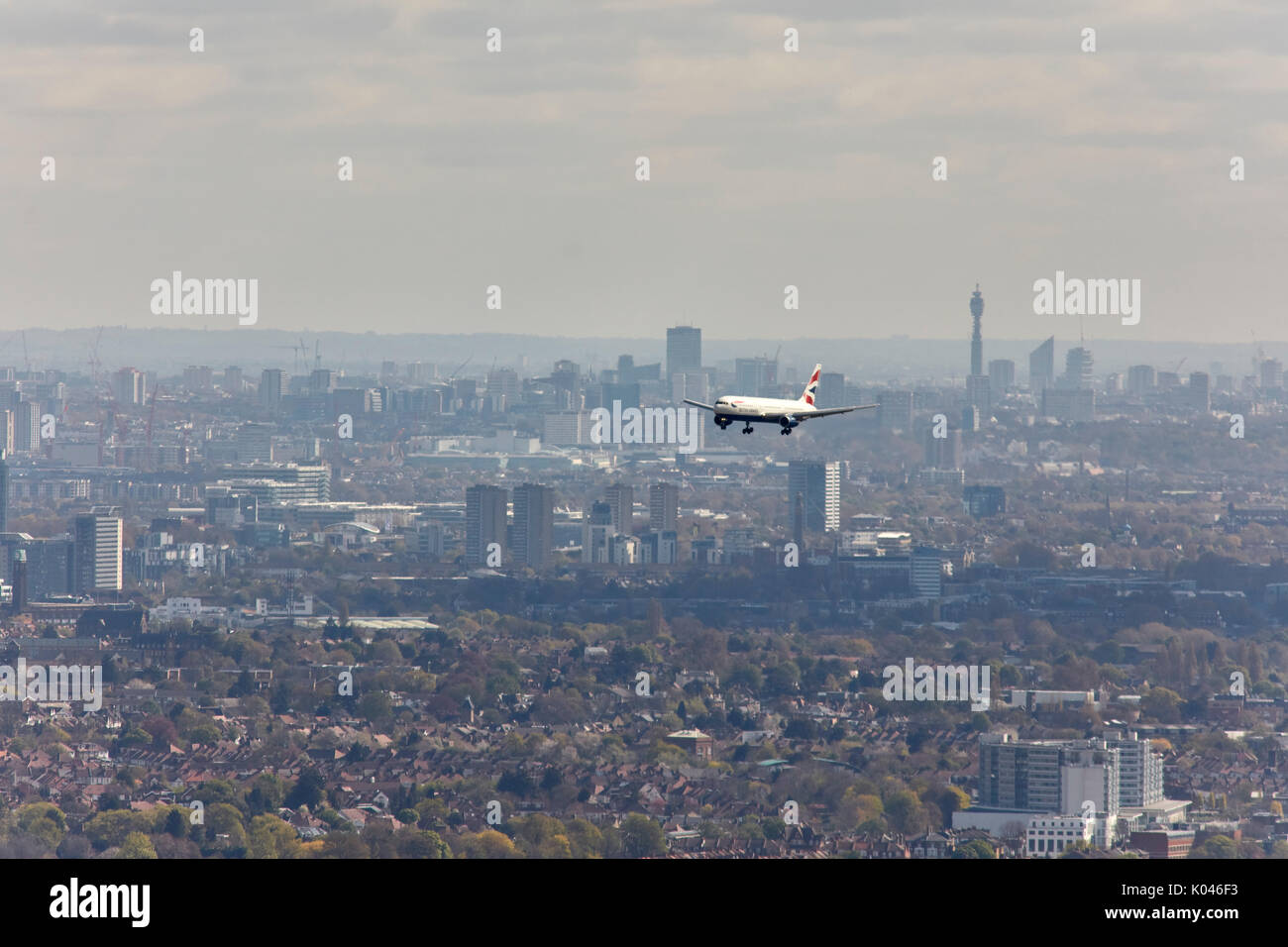 An aerial view of a commercial aircraft on approach to Heathrow with the skyline of London in the background - Stock Image
