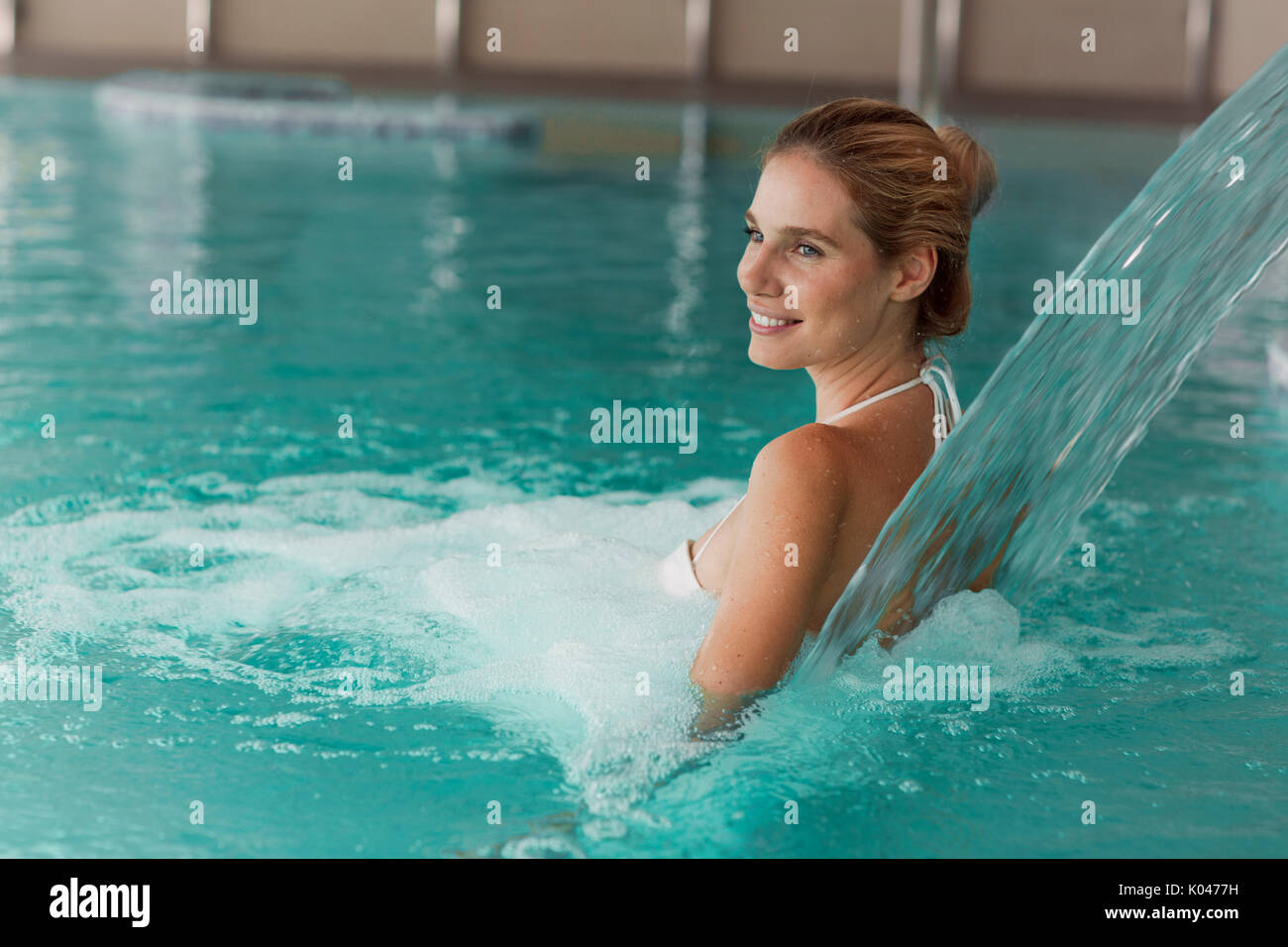 Portrait of beautiful woman relaxing in swimming pool - Stock Image