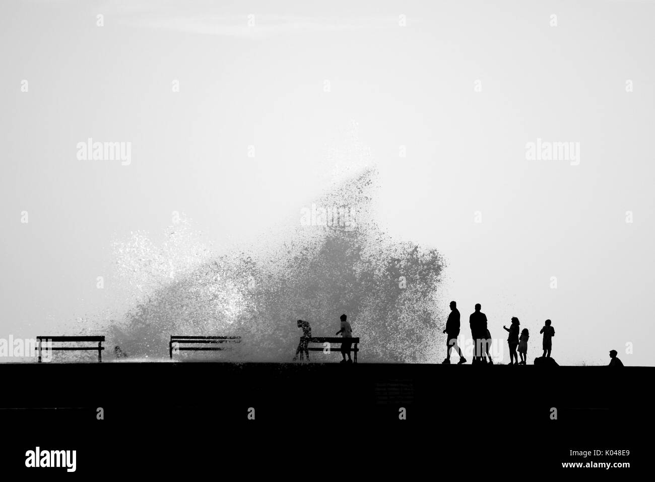 People silhouettes on the breakwater during sea splashing Stock Photo