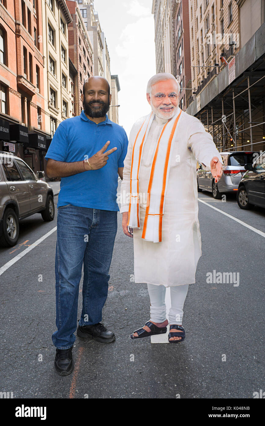 An Indian American with a life size cutout of the Prime Minister of India Narendra Modi poses at the start of the India Day Parade in New York City - Stock Image