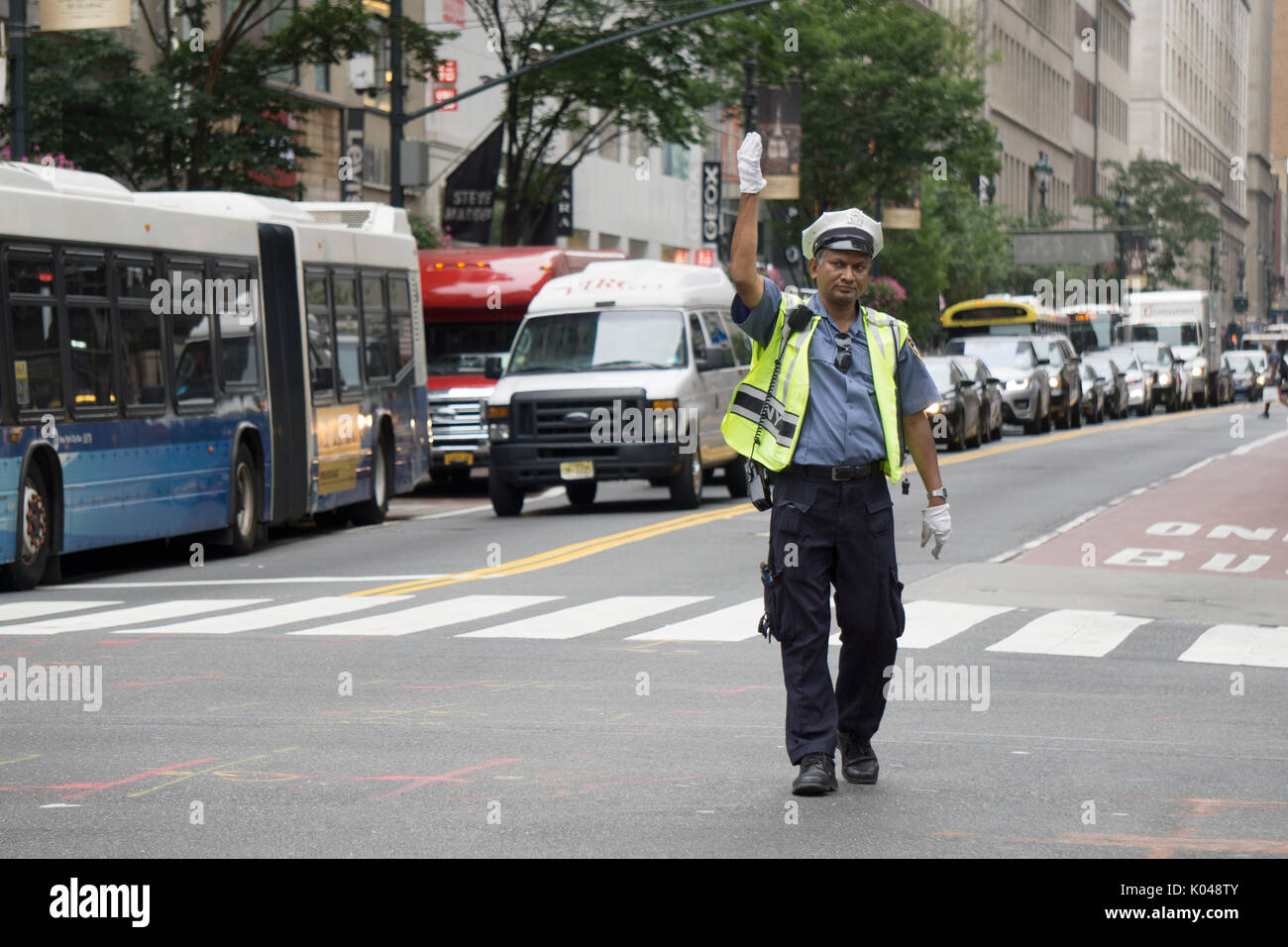 A Bangladeshi police officer directing automobile traffic on Broadway and 34th Street, Herlad Square, in Manhattan, New York City. - Stock Image