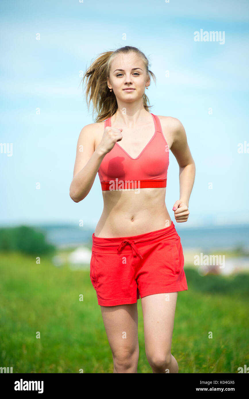 Young woman running summer park rural road. Outdoor exercises.  - Stock Image