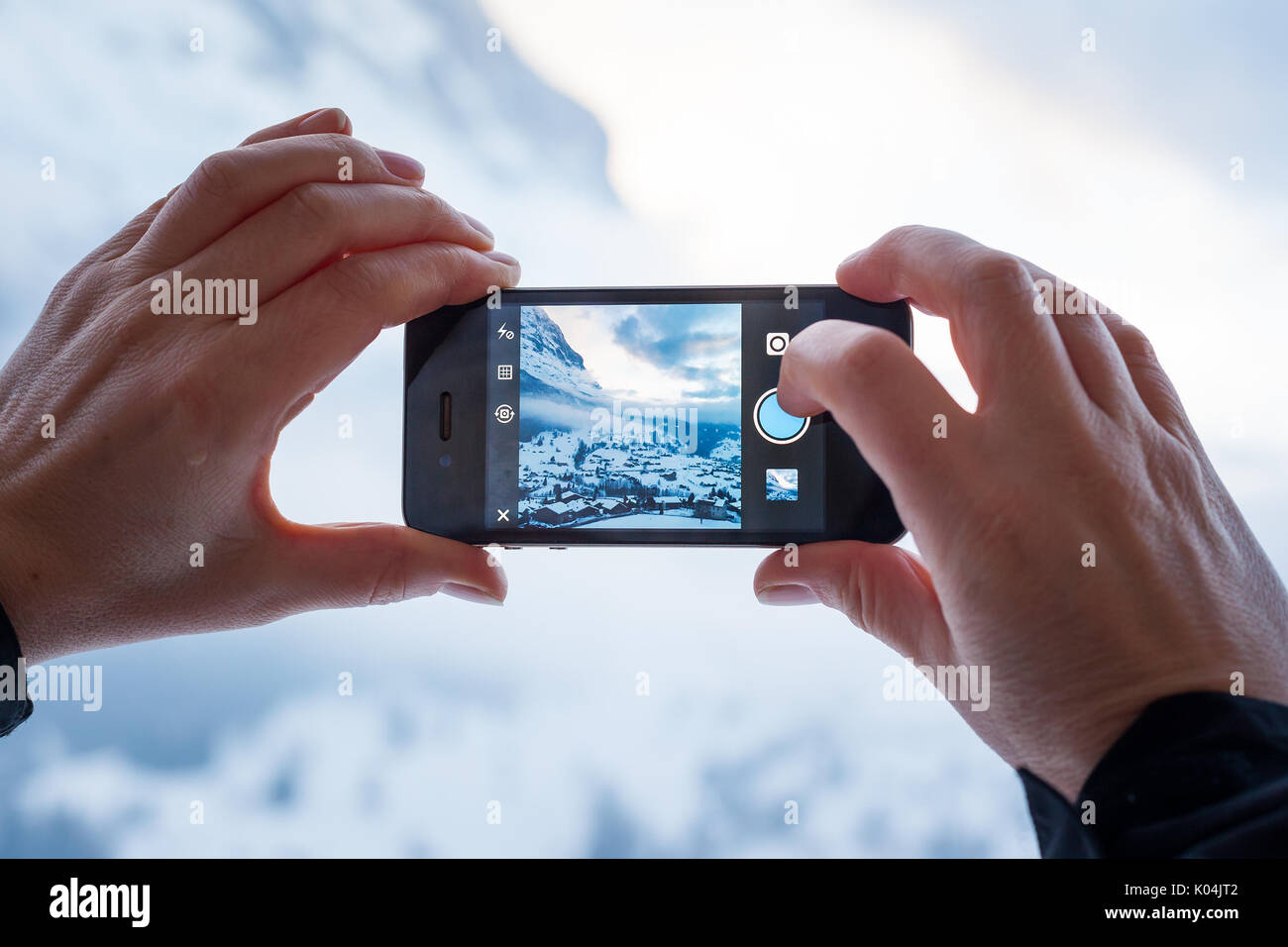 GRINDELWALD, SWITZERLAND - FEBRUARY 4, 2014: Woman taking a photograph of mountains using the Instagram App on an Apple iPhone. Instagram allows users - Stock Image