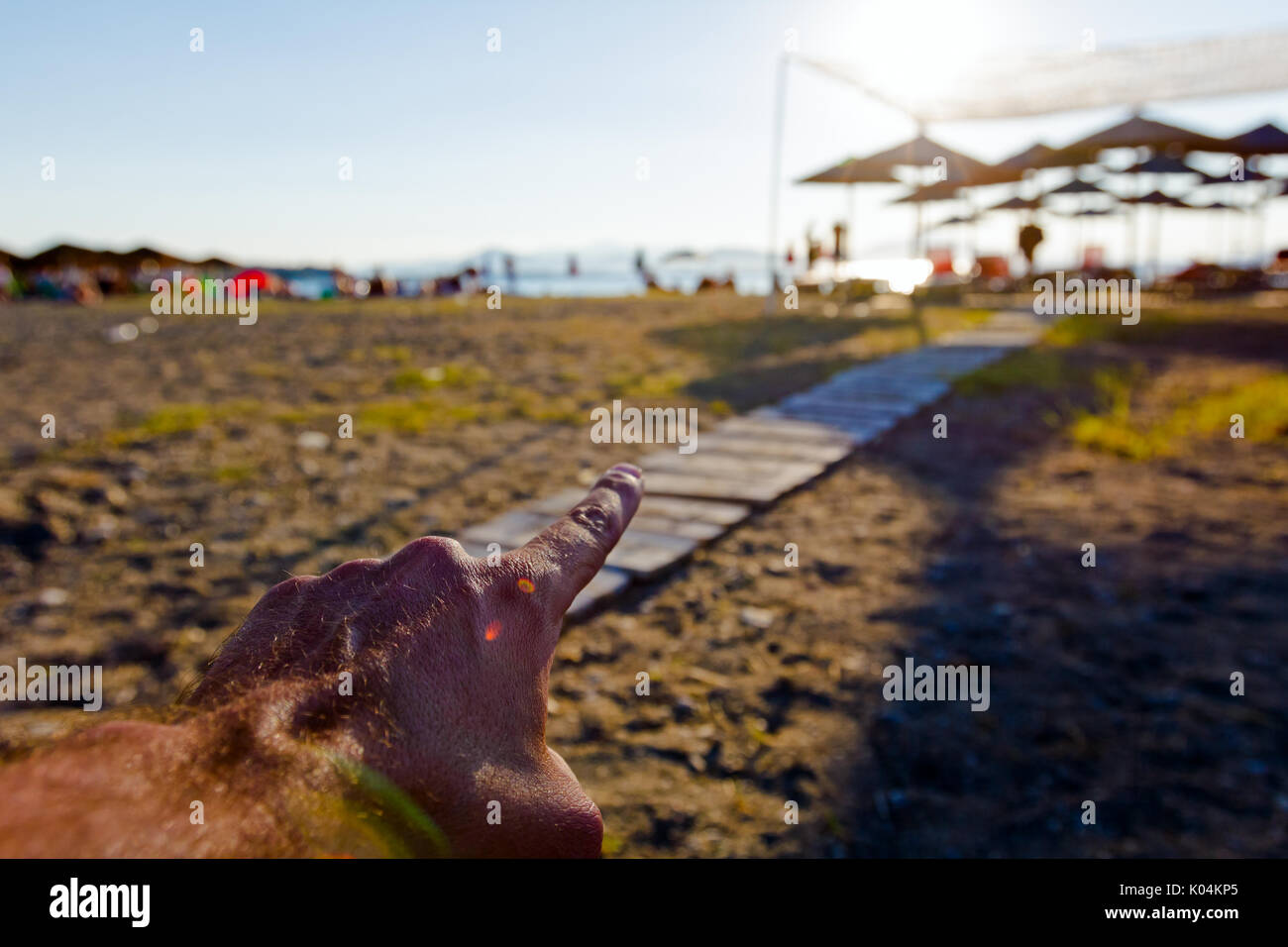 Hand is pointing with finger on wooden path through the sandy beach. - Stock Image