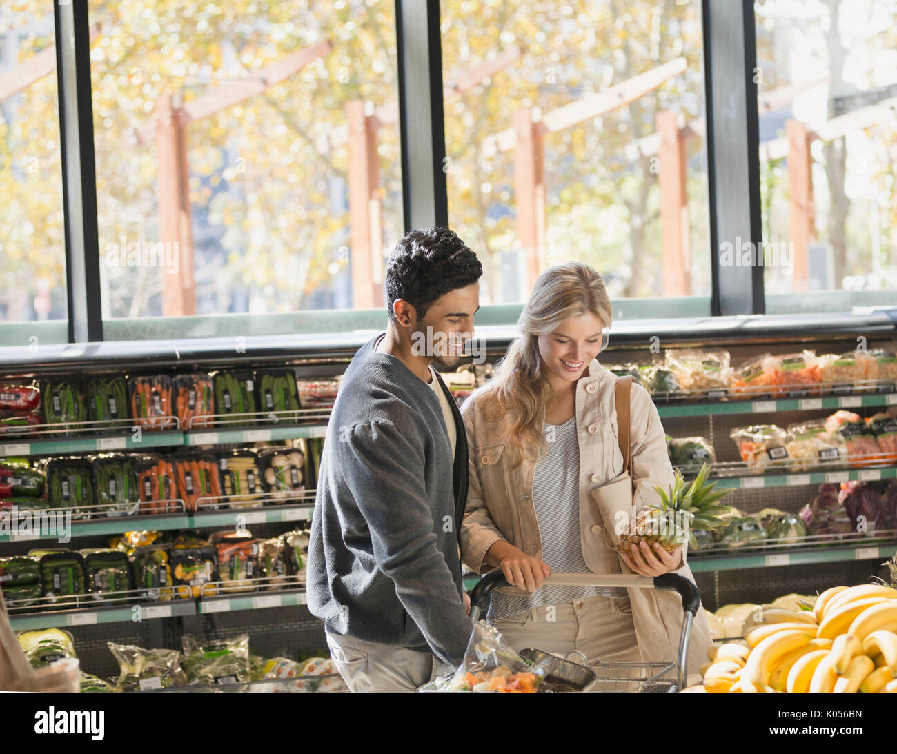 Smiling young couple grocery shopping, holding pineapple in market Stock Photo