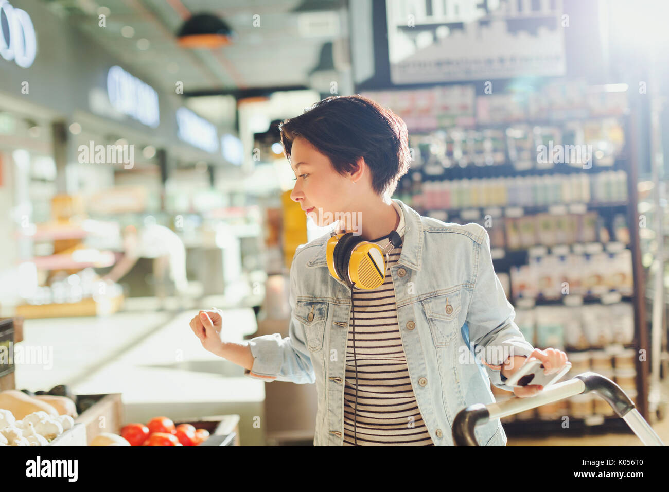 Young woman with headphones browsing, grocery shopping in market - Stock Image