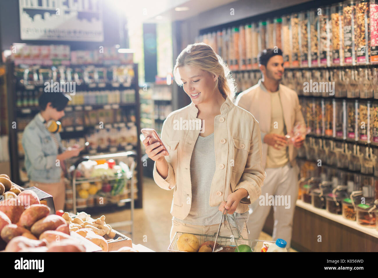 Young woman using cell phone, grocery shopping in market - Stock Image