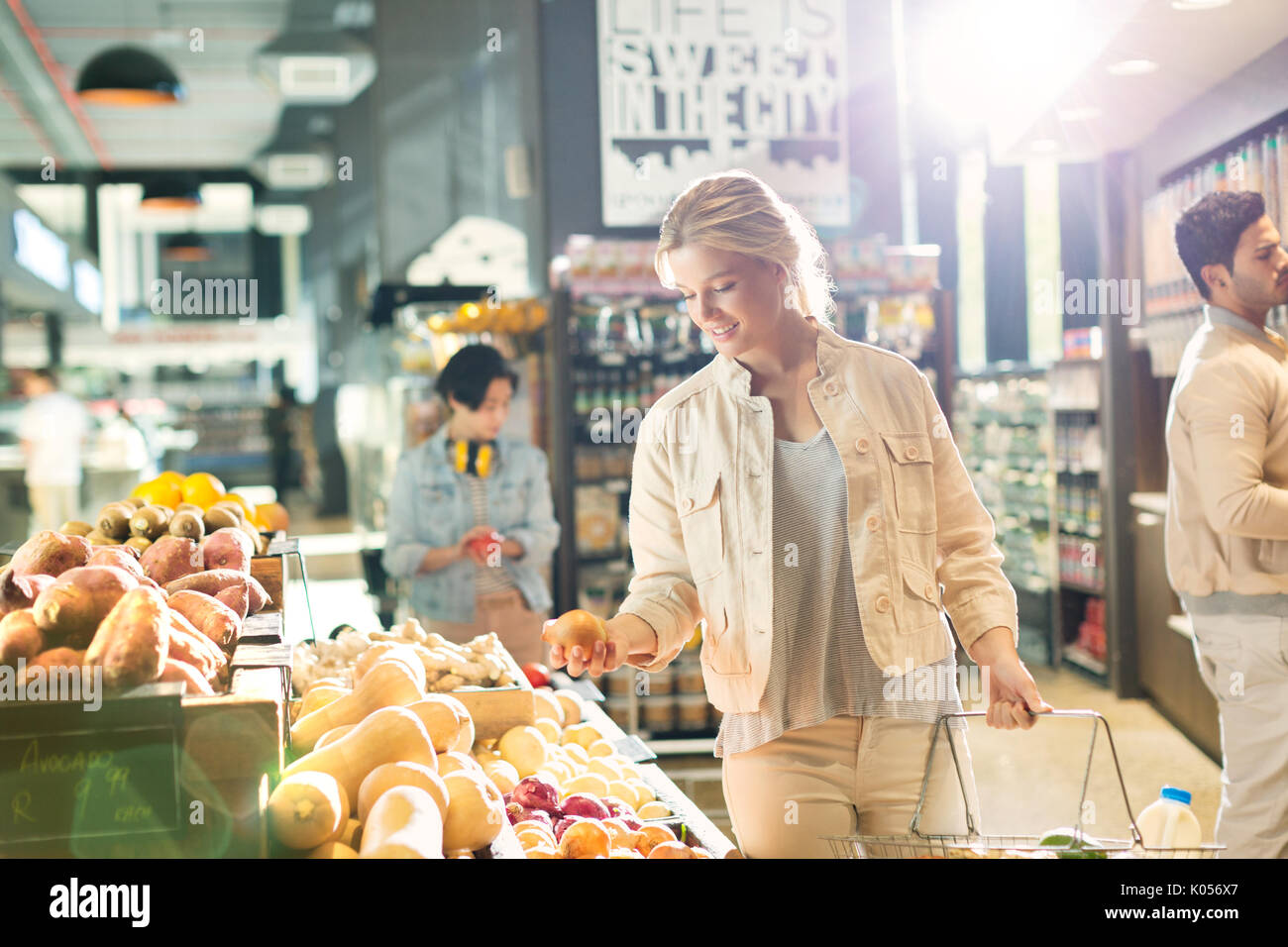 Young woman grocery shopping, browsing produce in market - Stock Image
