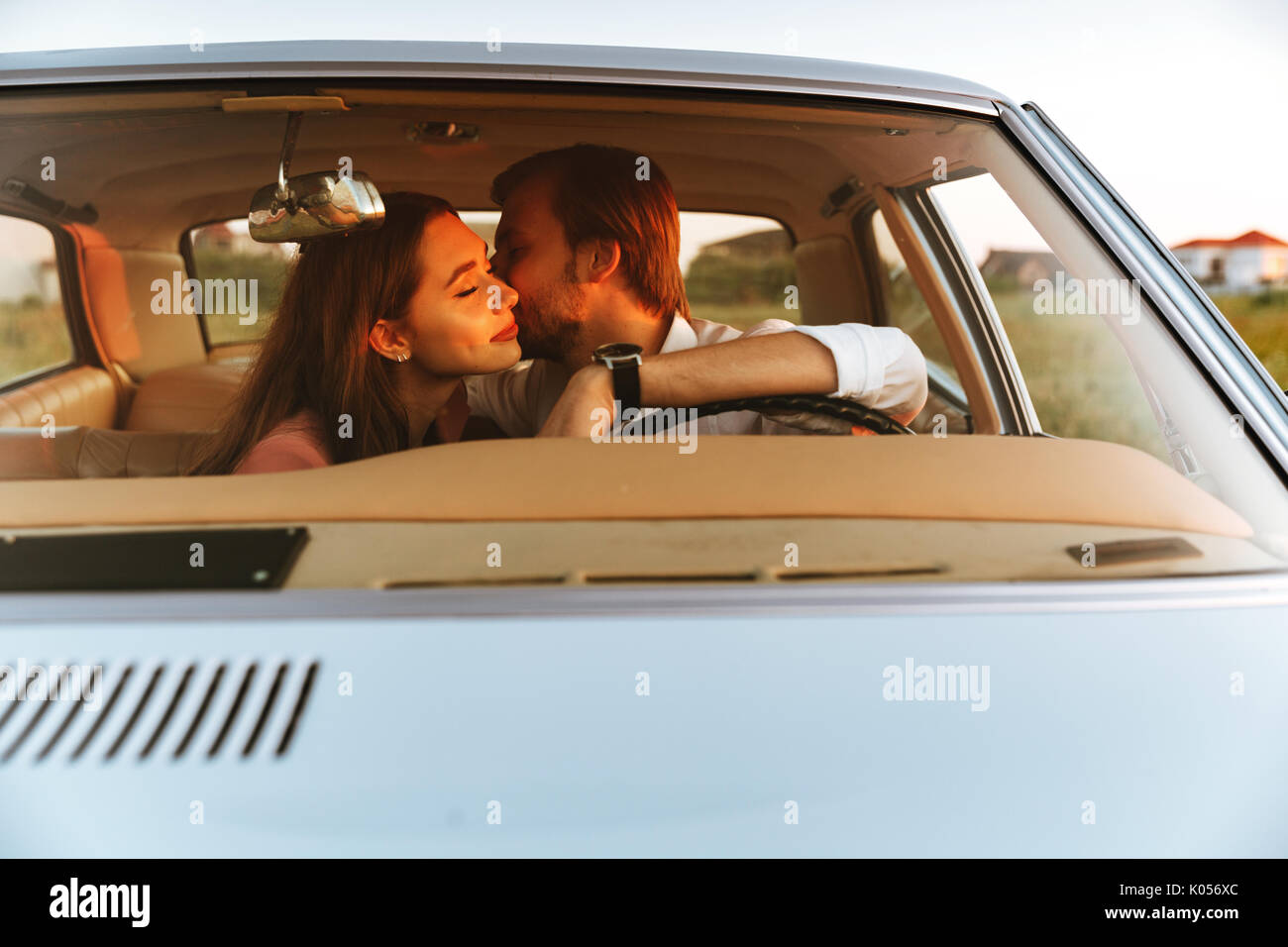Young happy couple kissing while sitting together inside a car. Front window view - Stock Image