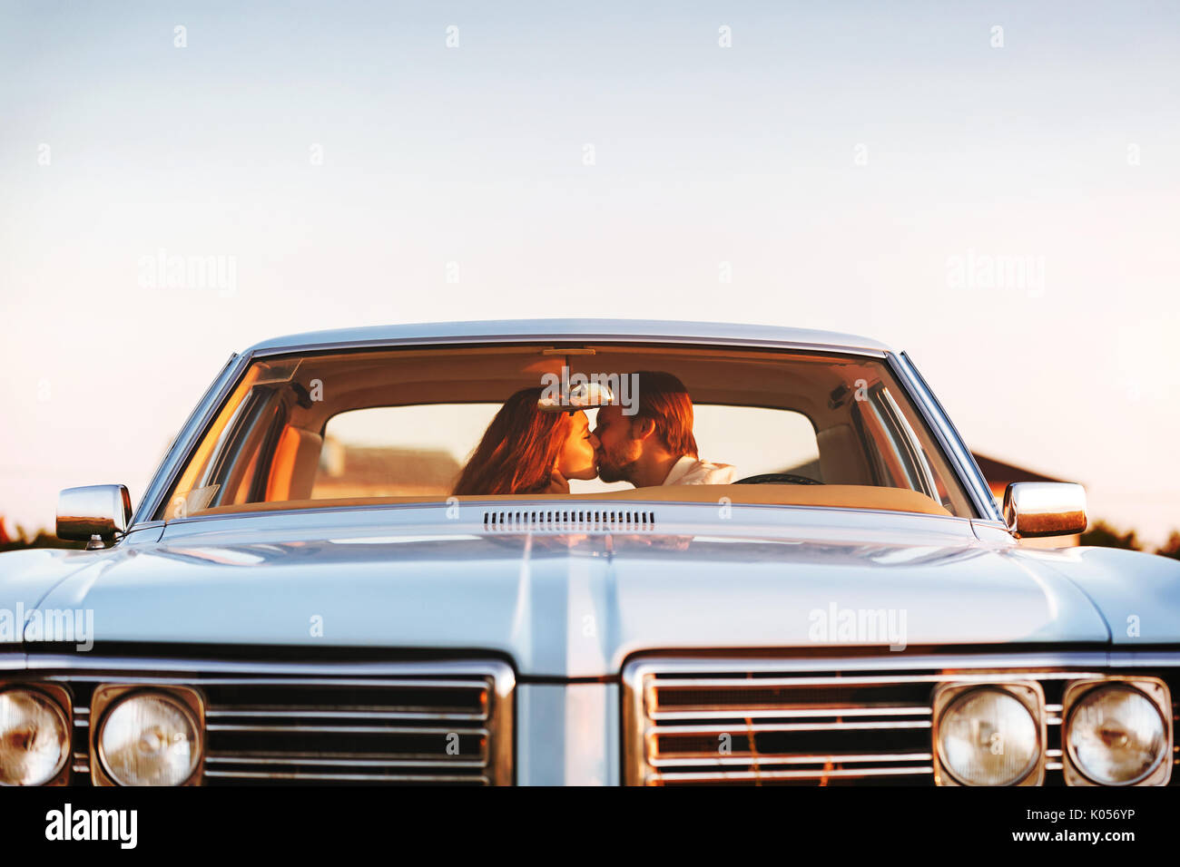 Beautiful young couple kissing while sitting together in an old retro car. Front window view - Stock Image