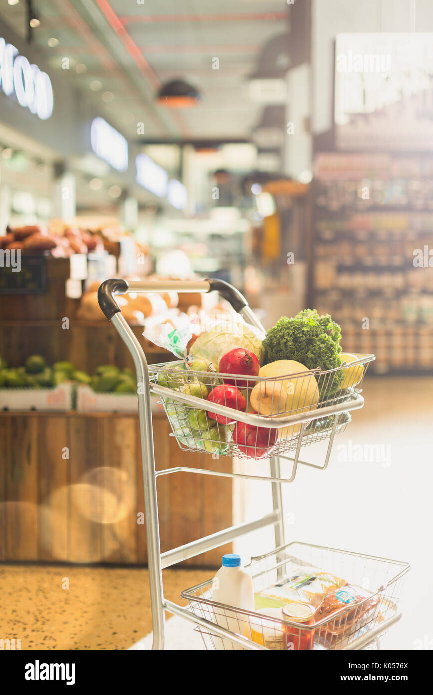 Produce and groceries in shopping cart in market Stock Photo