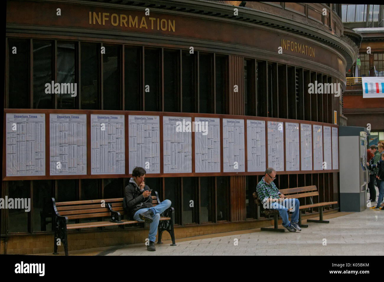 two men boys sitting on benches train time tables background using smart phone under wooden paneled information sign Glasgow central station concourse - Stock Image