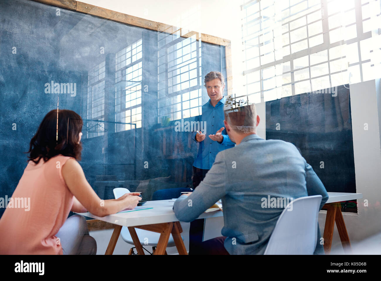 Office coworkers brainstorming together inside of a meeting room - Stock Image