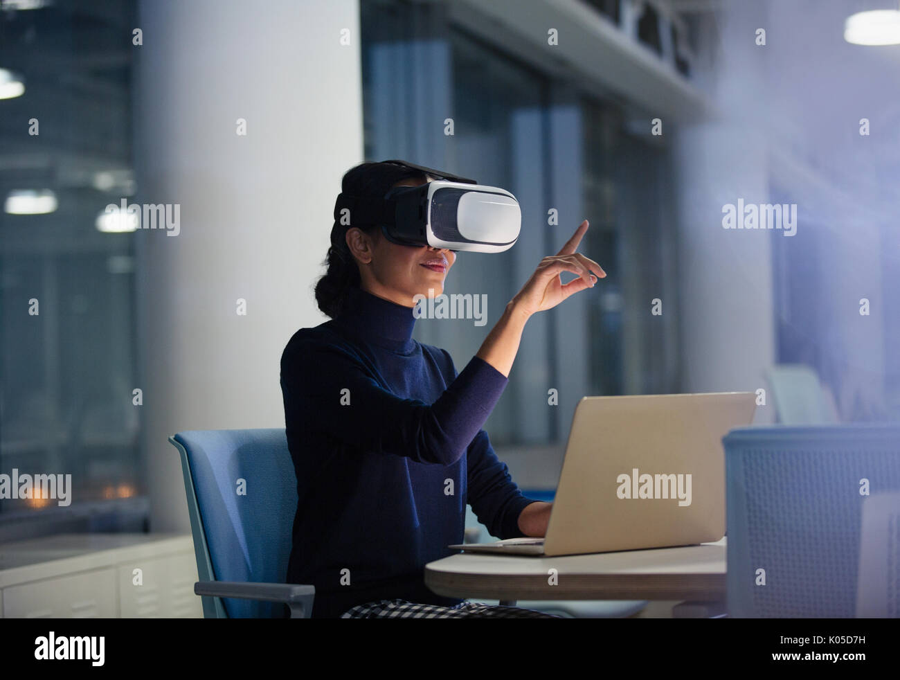 Businesswoman using virtual reality simulator at laptop in office - Stock Image