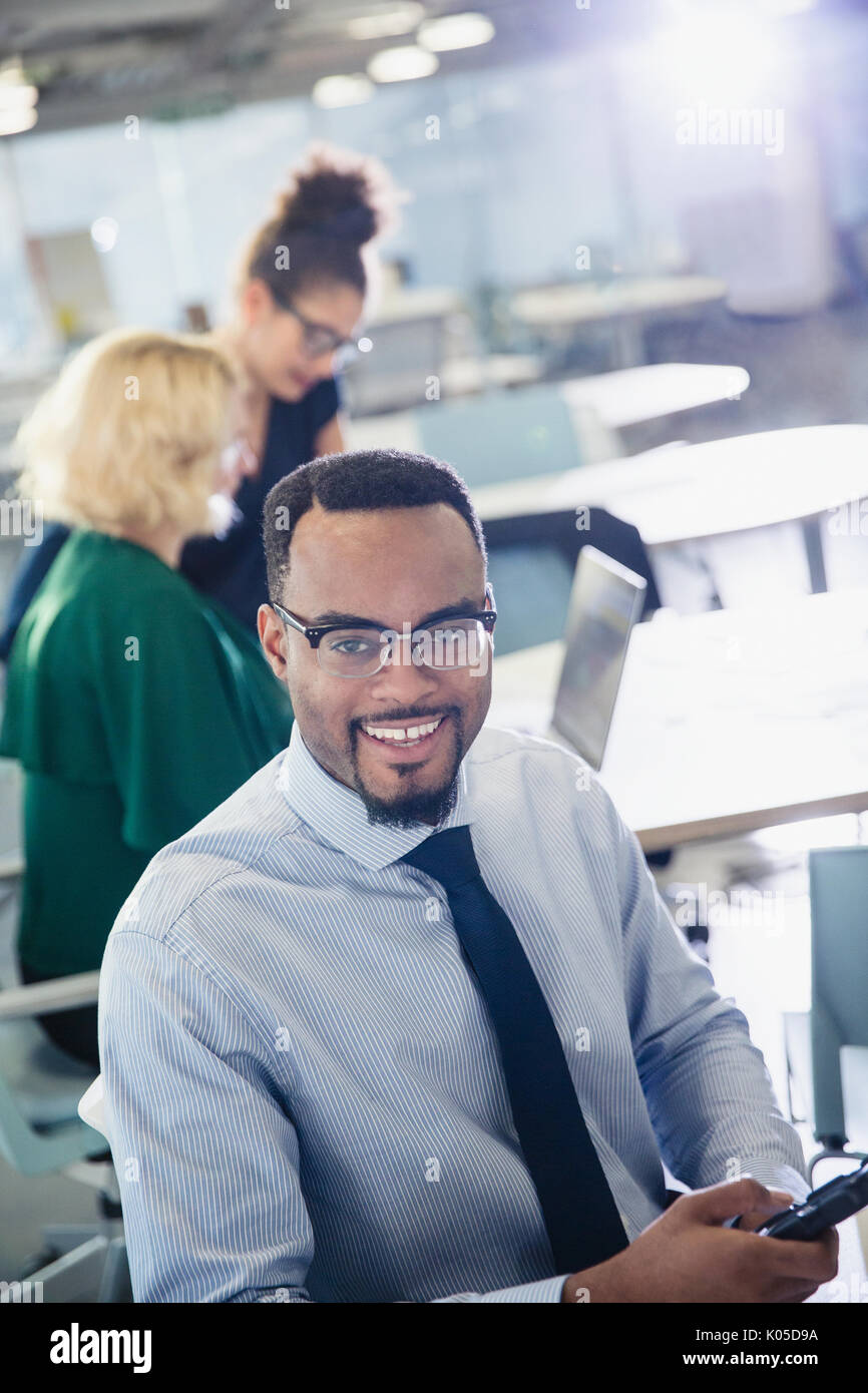 Portrait smiling businessman texting with cell phone in office - Stock Image