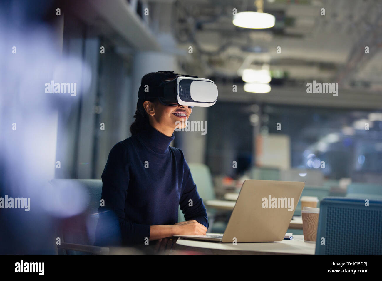 Businesswoman using virtual reality simulator at laptop in dark office - Stock Image