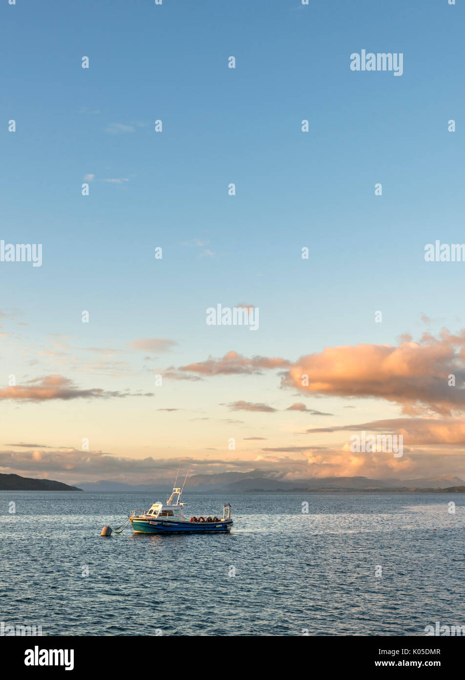 Boat moored in the bay in Craignure at sunset, Isle of Mull, Argyll and Bute, Scotland, UK - Stock Image