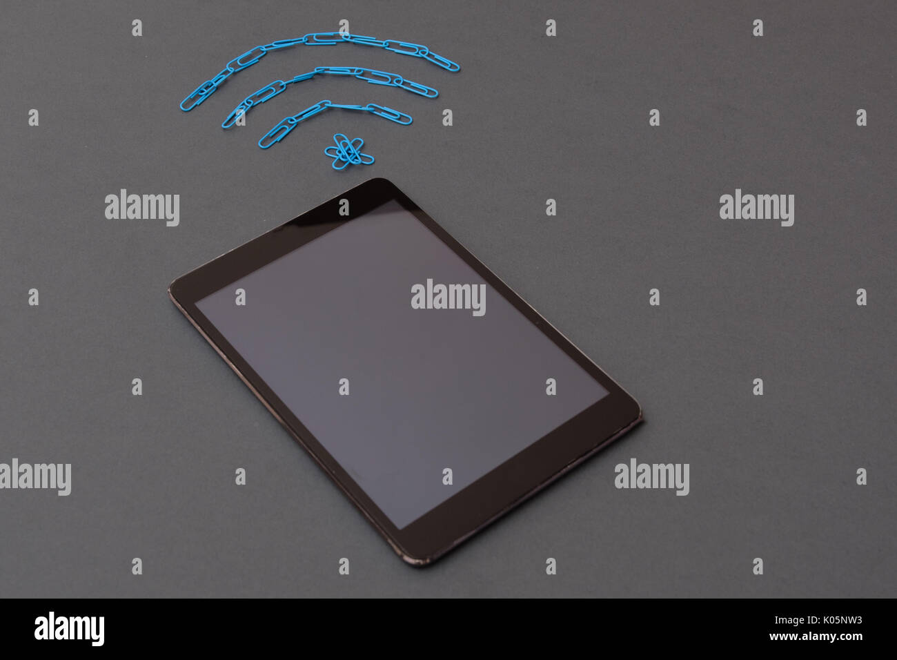 Wireless signal symbol made of paperclips and digital tablet - Stock Image