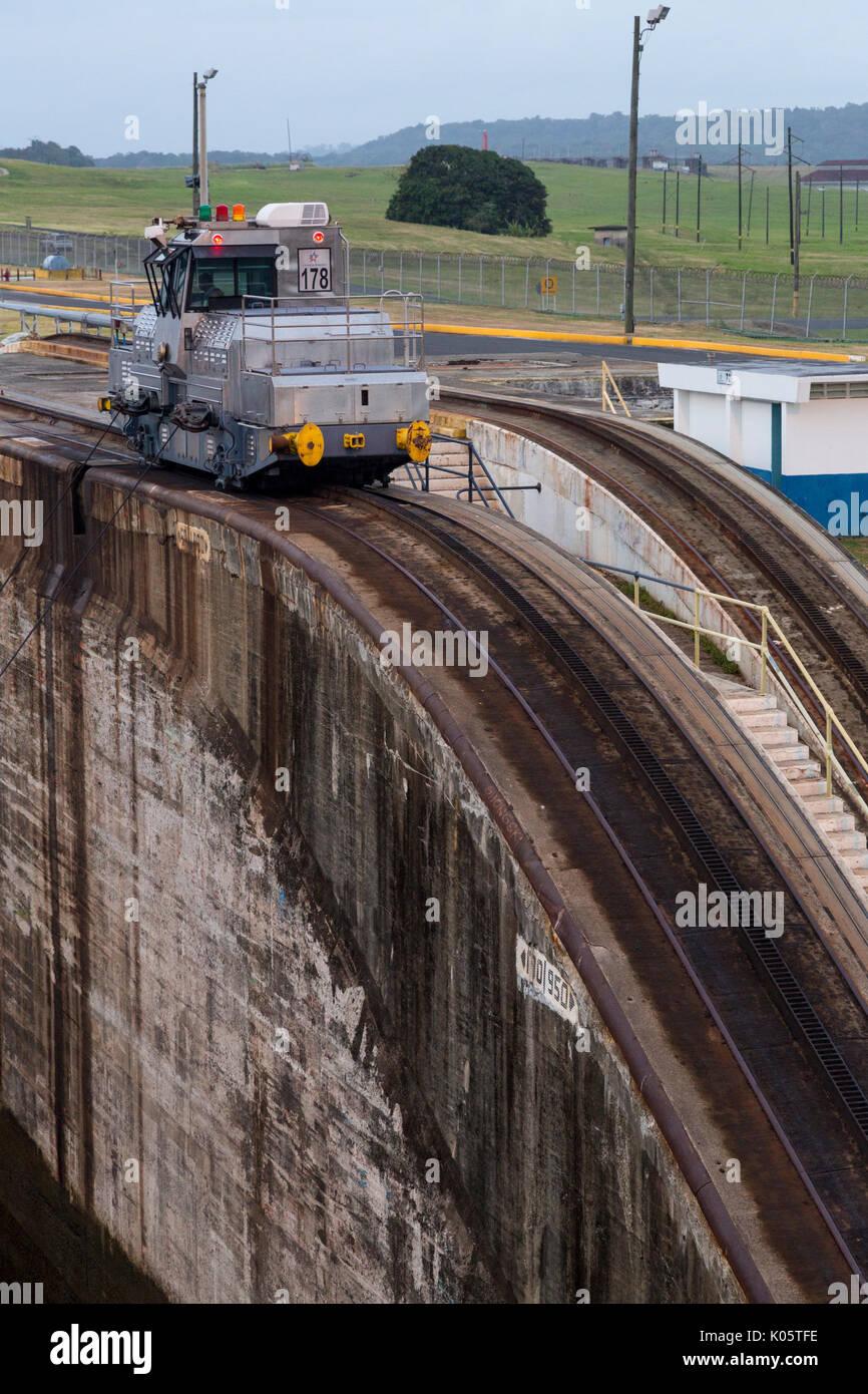 Panama Canal, Panama.  Entering First Lock, Caribbean Side, Heading toward Lake Gatun.  'Mule' Locomotive Pulling Ship Forward into the Lock. - Stock Image