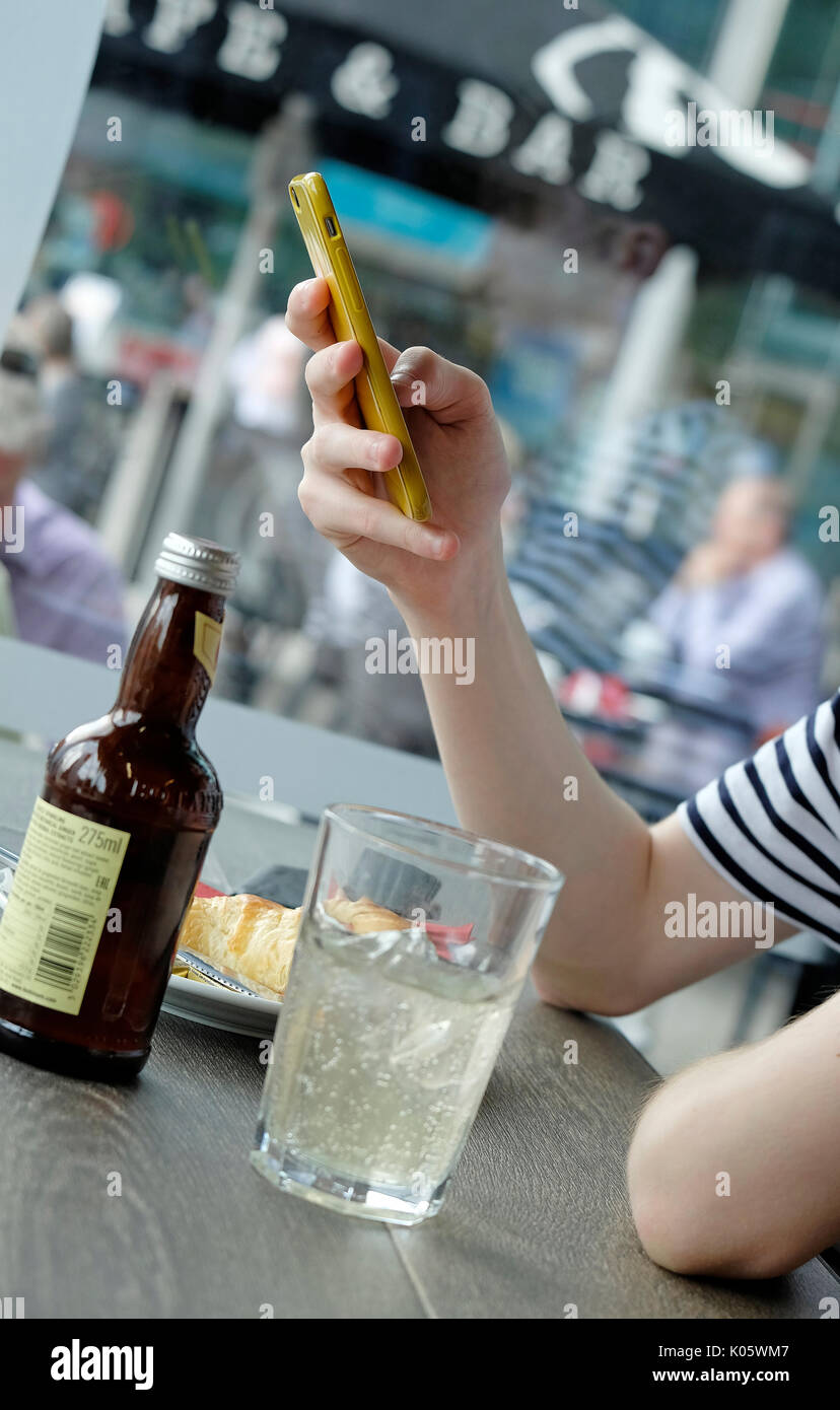 young teenage male using mobile phone in cafe - Stock Image