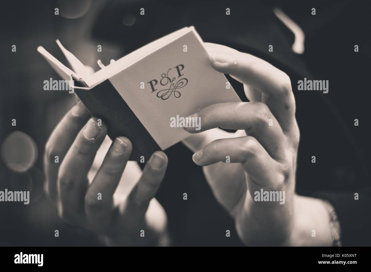 Close up of the hands of a college student holding and reading a miniature book in the Special Collections department of a University library, the book labeled 'P and P', for Pride and Prejudice, 2016. - Stock Image
