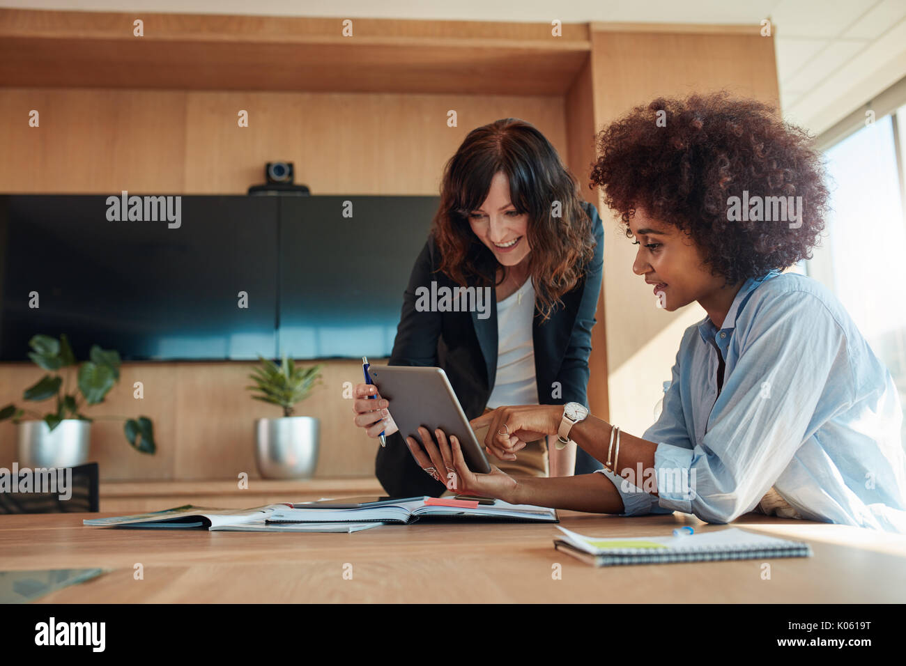 African businesswoman showing something on digital tablet to her female colleague while sitting at her desk. Professional employees discussing ideas o - Stock Image