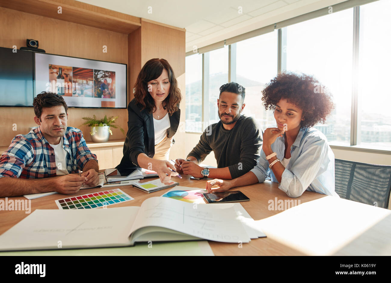 Creative people looking at project plan laid out on table. Mixed race business associates discussing new project plan in modern office. - Stock Image