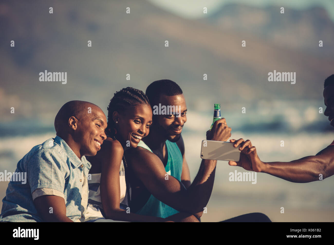 Group of happy friends having fun together and taking selfie using mobile phone. Self portrait at beach party. - Stock Image