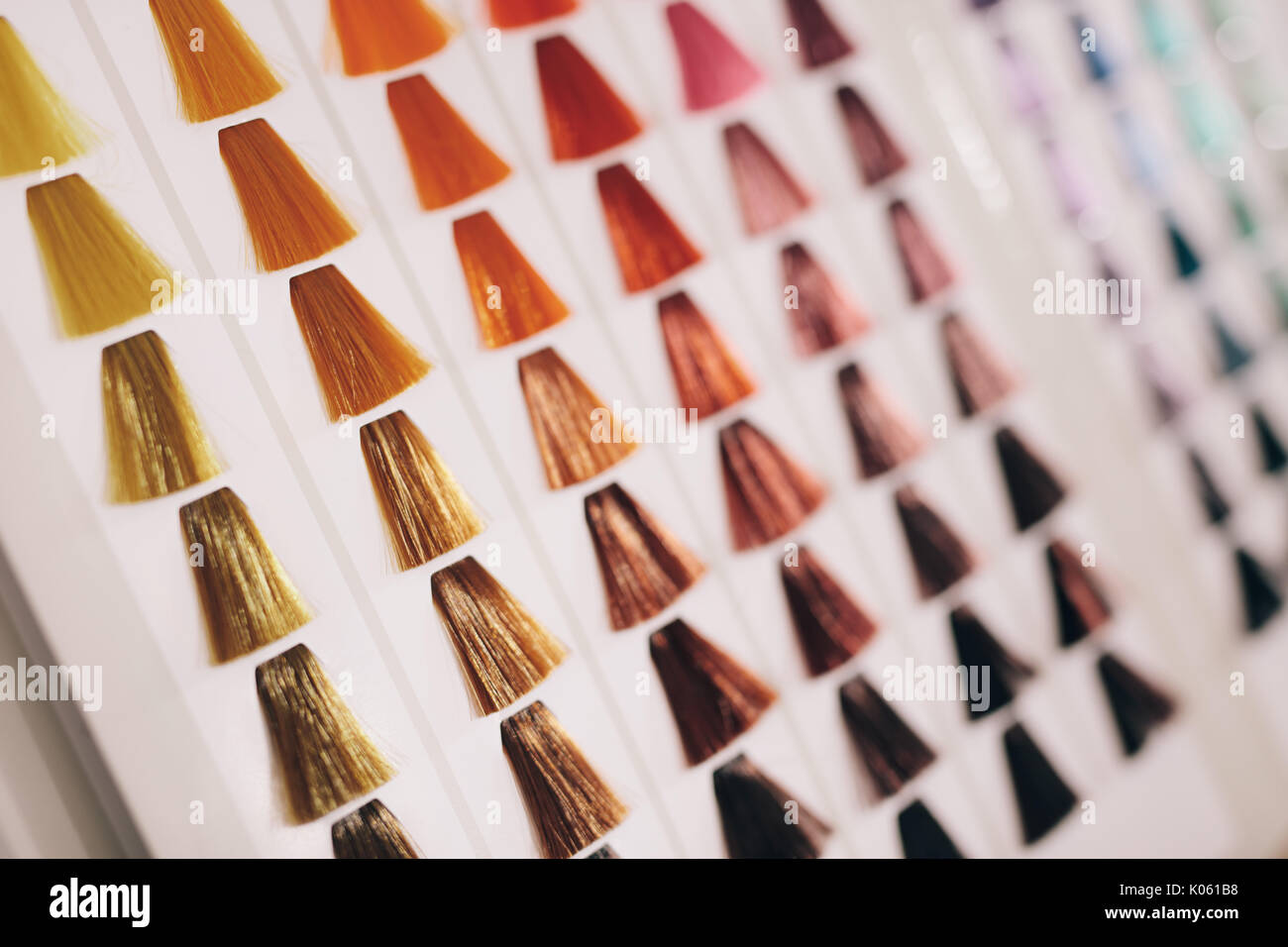 Closeup of hair samples with different color shades on a card. Hair color choice chart on display at salon. - Stock Image