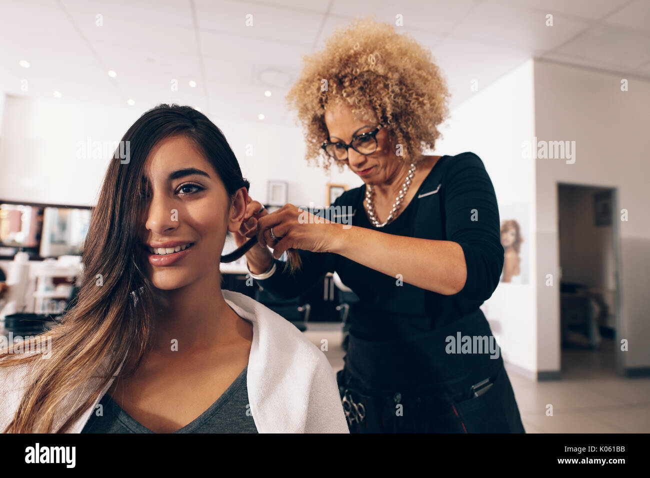 Woman hairdresser at work in salon. Young woman getting a stylish hairdo done at salon. - Stock Image