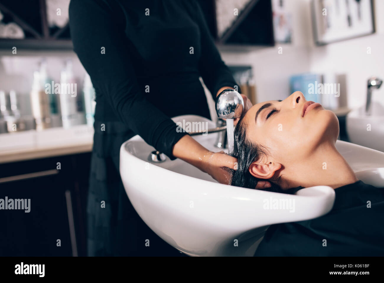 Closeup of hairdresser giving hair wash service to a customer at the salon. Woman getting hair spa treatment done at hair salon - Stock Image