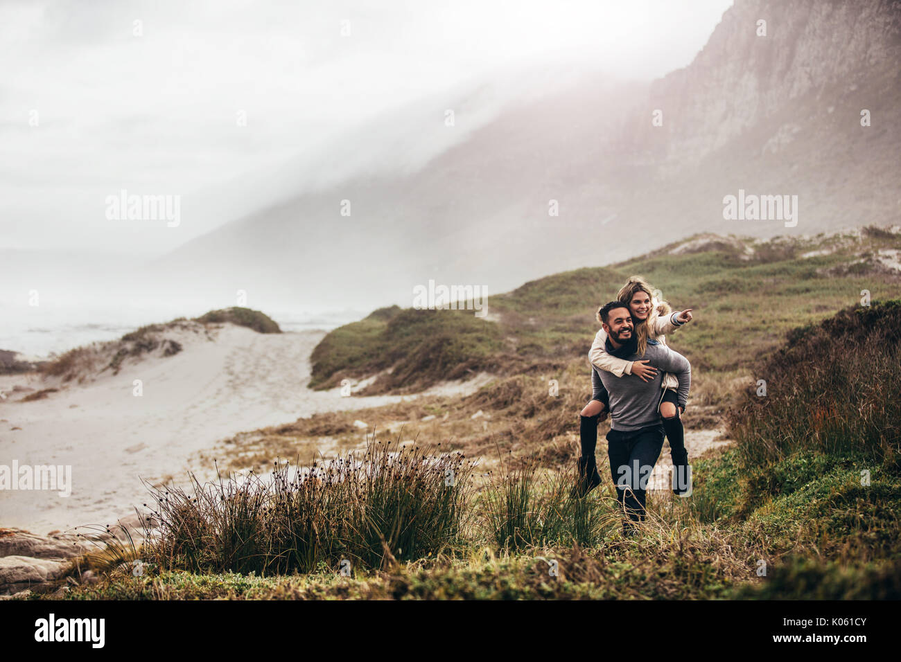 Outdoor shot of man giving woman piggyback on winter beach. Man carrying woman oh his back pointing away. - Stock Image