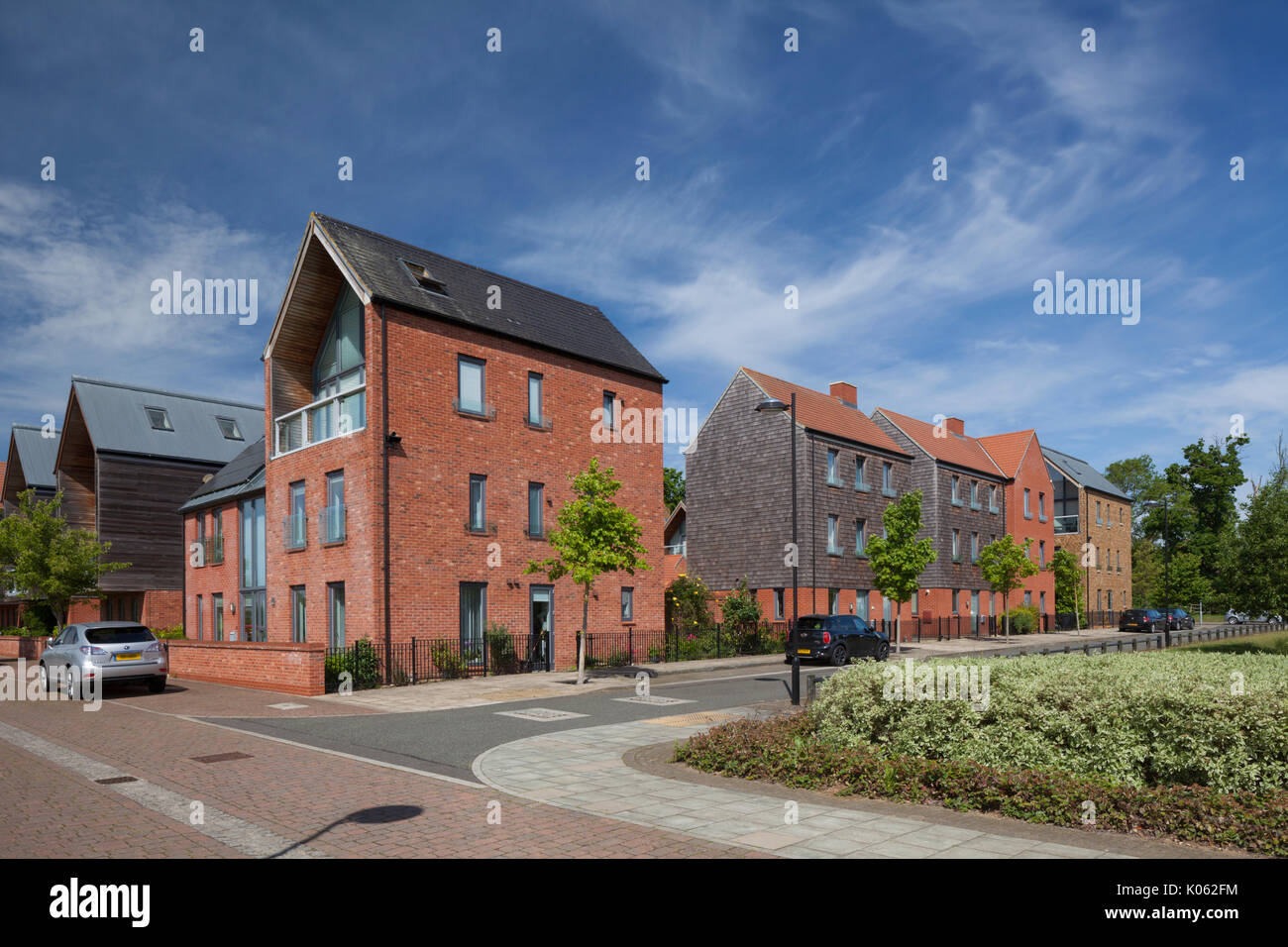 Contemporary Eco-designed modern suburban housing development with trees lining street at Upton, South West District, Northampton, England. - Stock Image