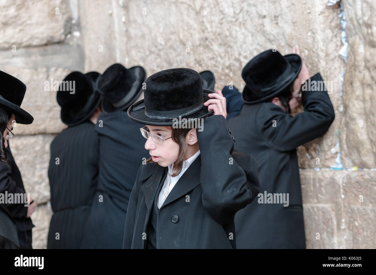 A Hasid boy among others at the Western Wall. This denomination of Orthodox Judaism concentrates on spiritual contact with God through vivid praying. - Stock Image