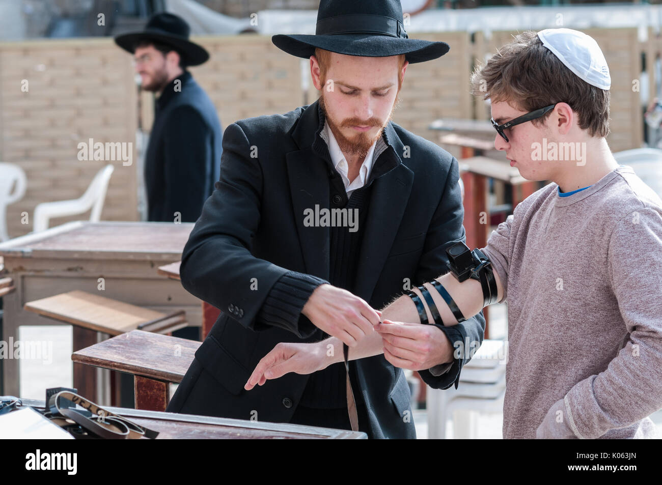 An observant Jew wraps a hand-tefillin on an arm of another man at the Western Wall. Tefillin are a set of two boxes with passages from the Torah. - Stock Image