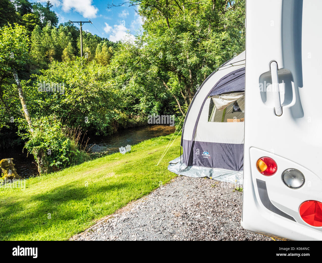A caravan with a small porch awning pitched along the banks of the River Exe in Exmoor, Somerset. - Stock Image