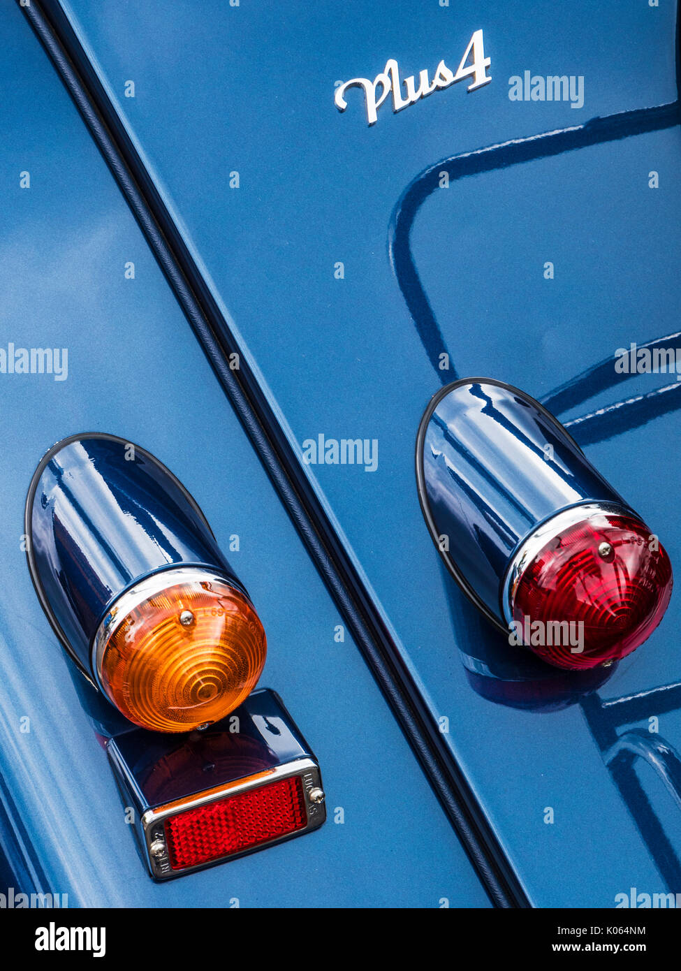 An abstract image of the badge and tail lights of a blue classic vintage Morgan Plus 4 sports car. - Stock Image