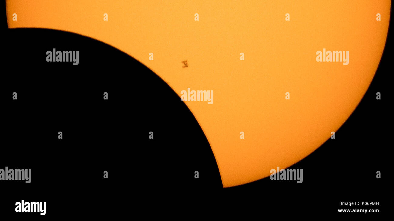 The International Space Station, with a crew of six onboard, is seen in silhouette as it transits the Sun at roughly five miles per second during a partial solar eclipse, Monday, Aug. 21, 2017 from Ross Lake, Northern Cascades National Park, Washington.  Onboard as part of Expedition 52 are: NASA astronauts Peggy Whitson, Jack Fischer, and Randy Bresnik; Russian cosmonauts Fyodor Yurchikhin and Sergey Ryazanskiy; and ESA (European Space Agency) astronaut Paolo Nespoli. A total solar eclipse swept across a narrow portion of the contiguous United States from Lincoln Beach, Oregon to Charleston,  - Stock Image