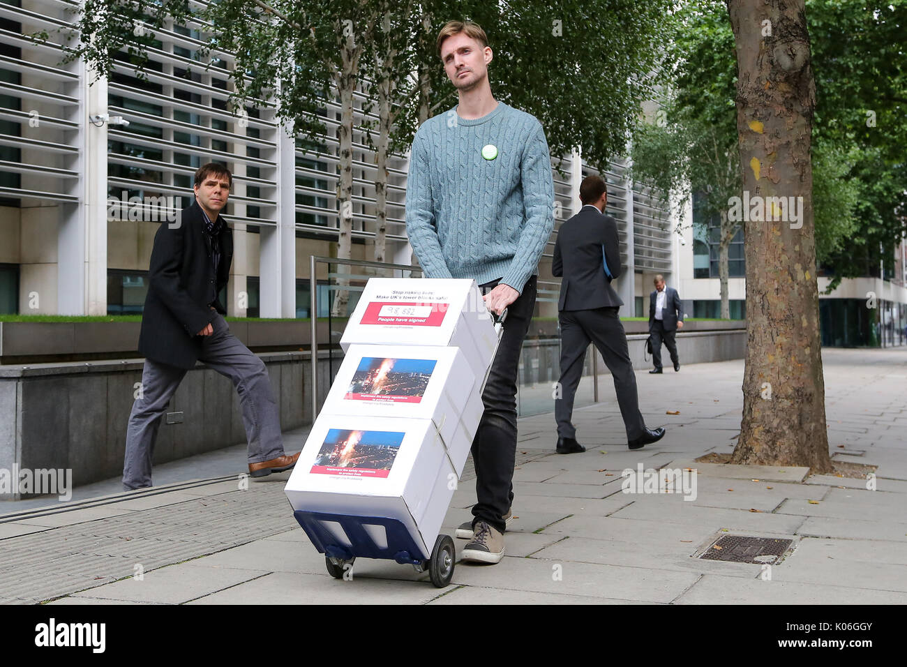 Westminster. London, UK. 22nd Aug, 2017. John Tyson, the founder of a petition to bring in fire safety regulations to make Britain's tower blocks safer poses for media before handing in the petition to the Department for Communities and Local Government (DCLG). The petition of 98,882 signatures to the DCLG follows the critical findings of the 2013 coroner's report on the 2009 Lakanal fire, which highlighted issues that could have prevented Grenfell, the petition is asking for the immediate implementation of recommendations from that report. Credit: Dinendra Haria/Alamy Live News - Stock Image