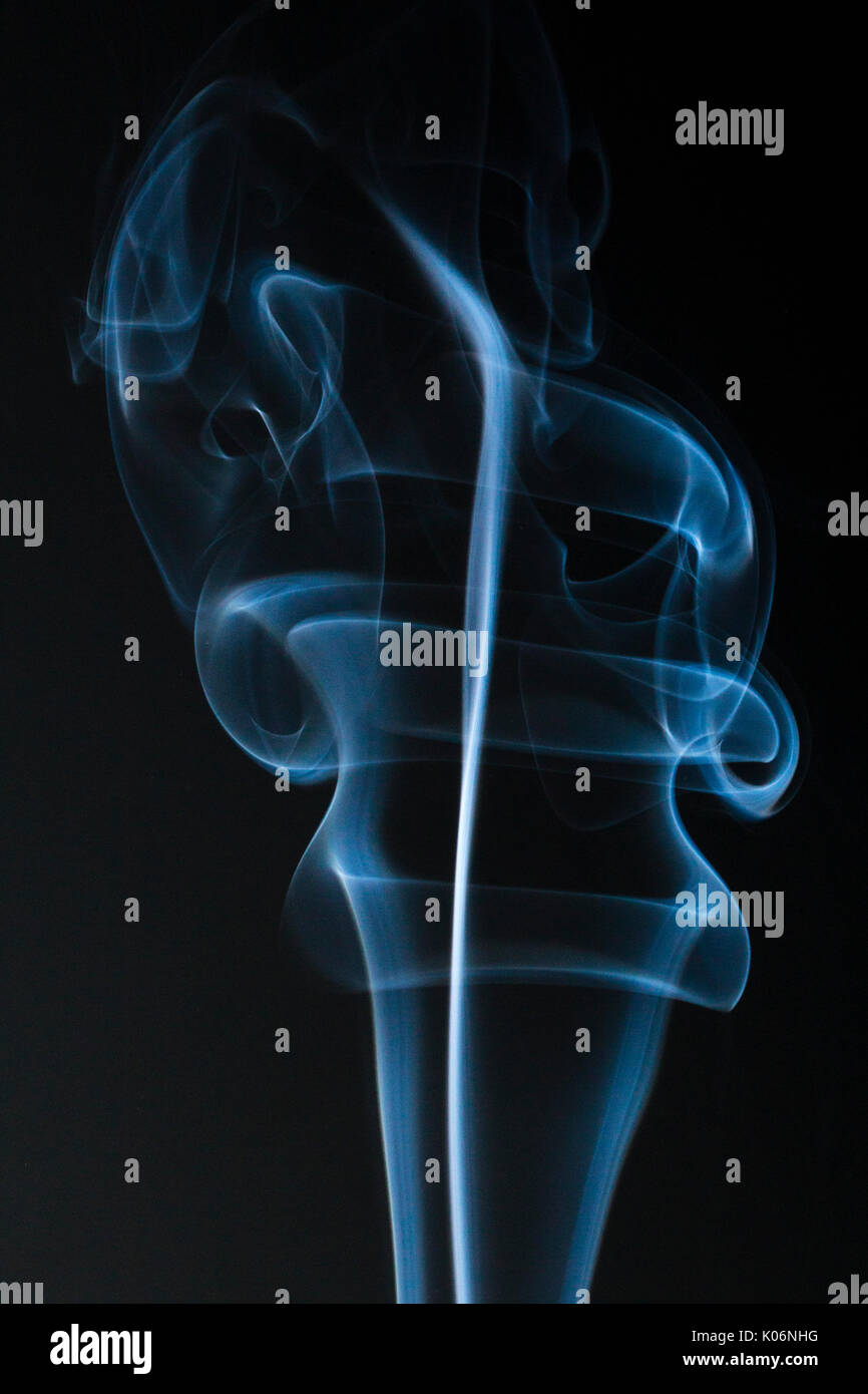 Blue lit Smoke rising forming abstract patterns against black background. - Stock Image