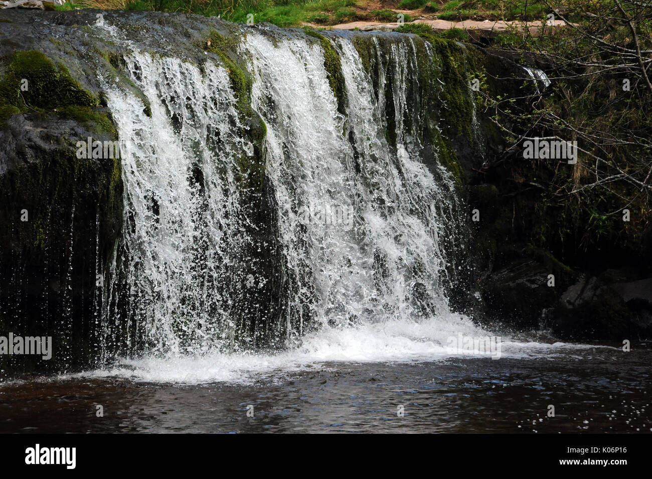 The upper of the two small waterfalls on the Afon Caerfanell near its confluence with the Nant Bwrefwr. - Stock Image